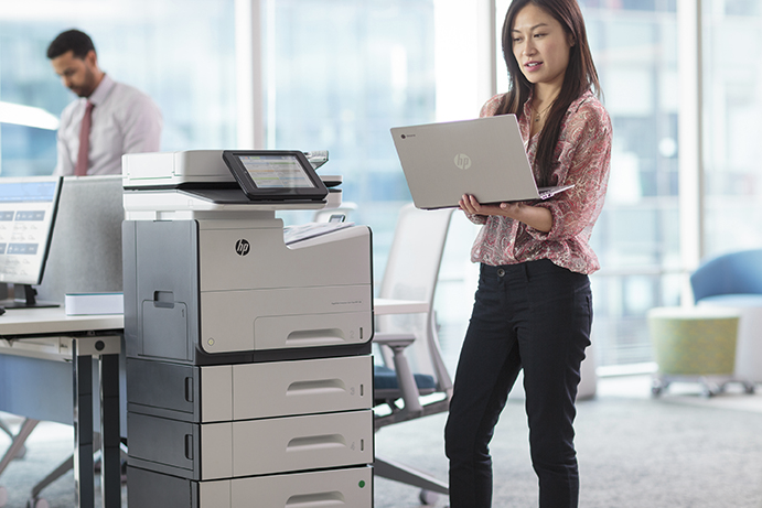 Woman using her HP Chromebook 13 G1 to print to a HP PageWide Enterprise Color MFP 586z.