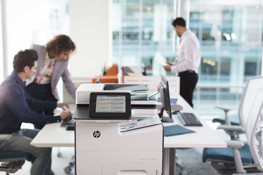 Office workers looking over prints from the HP PageWide Enterprise Color MFP 586z.